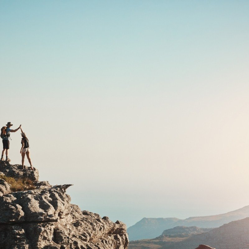 Two people standing on the top of a mountain
